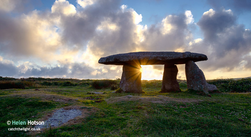 A starburst of sun gleaming through tLanyon Quoit an ancient neo